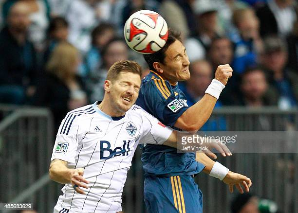 Jordan Harvey of the Vancouver Whitecaps FC and Stefan Ishizaki of the Los Angeles Galaxy head the ball during their MLS game April 19 2014 in...