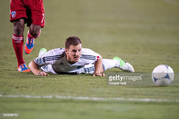 Jordan Harvey of the Vancouver Whitecaps FC is tackled while chasing the ball against FC Dallason September 15 2012 at FC Dallas Stadium in Frisco...
