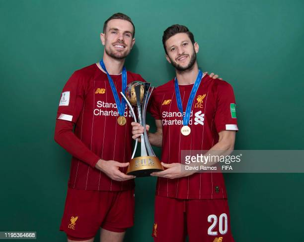 Jordan Henderson and Adam Lallana of Liverpool pose with the Club World Cup trophy after the FIFA Club World Cup Qatar 2019 Final match between...