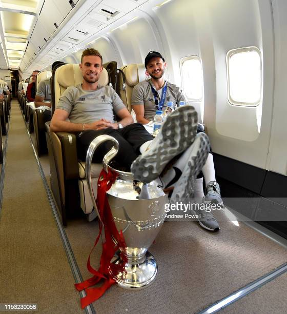 Jordan Henderson and Adam Lallana of Liverpool with the UEFA Champions League trophy during the flight home from winning the UEFA Champions League on...