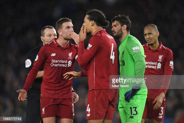 Jordan Henderson and Virgil van Dijk of Liverpool cover their mouths as they communicate during the Premier League match between Brighton Hove Albion...
