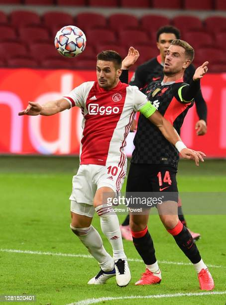 Jordan Henderson captain of Liverpool with Dusan Tadic of Ajax during the UEFA Champions League Group D stage match between Ajax Amsterdam and...