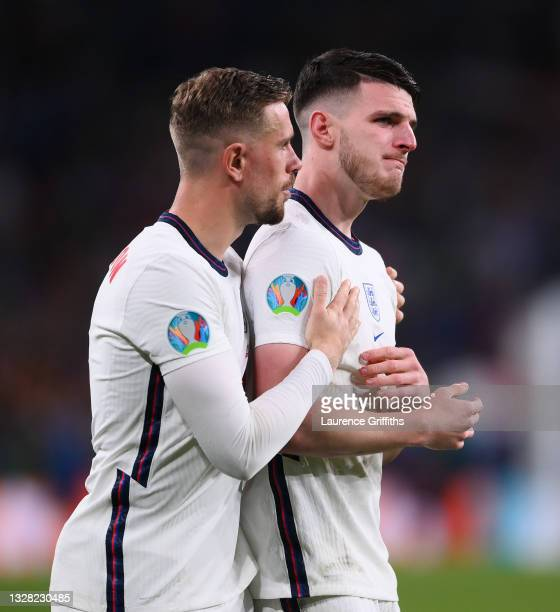 Jordan Henderson of England consoles teammate Declan Rice following defeat in the UEFA Euro 2020 Championship Final between Italy and England at...