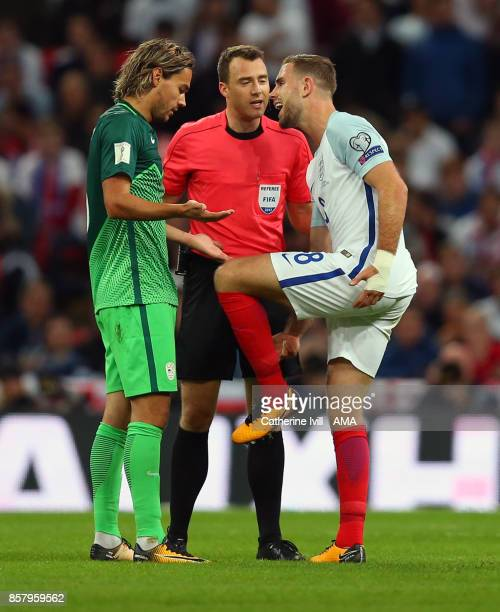 Jordan Henderson of England has words with Rene Krhin of Slovenia as referee Felix Zwayer watches during the FIFA 2018 World Cup Qualifier between...