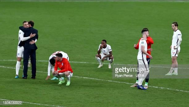 Jordan Henderson of England is consoled by Gareth Southgate, Head Coach of England as Jadon Sancho, Mason Mount, Raheem Sterling, Declan Rice and...