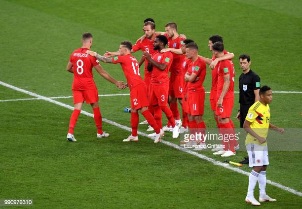 Jordan Henderson of England looks dejected and is consoled by teammates after missing his penalty as other players look on from the the halfway line...