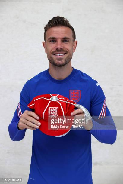 Jordan Henderson of England poses for a photograph holding an England cap at St George's Park on June 08, 2021 in Burton upon Trent, England.