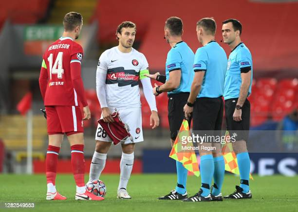 Jordan Henderson of Liverpool and Erik Sviatchenko of FC Midtjylland exchange pennants ahead of the UEFA Champions League Group D stage match between...