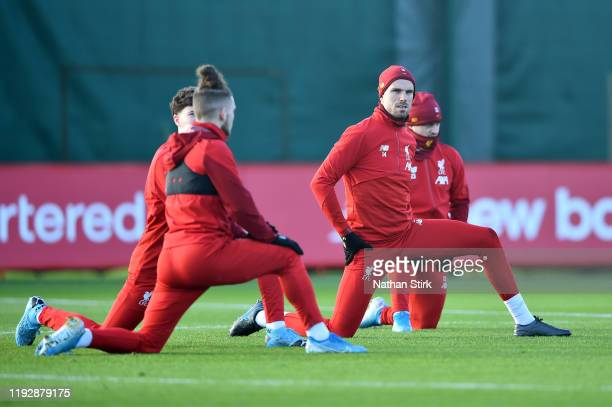 Jordan Henderson of Liverpool and his team mates stretches during a training session ahead of their UEFA Champions League Group E match against RB...