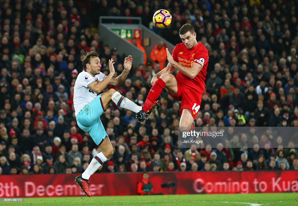 Jordan Henderson of Liverpool and Mark Noble of West Ham United compete for the ball during the Premier League match between Liverpool and West Ham United at Anfield on December 11, 2016 in Liverpool, England.