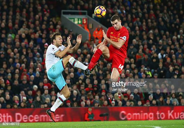Jordan Henderson of Liverpool and Mark Noble of West Ham United compete for the ball during the Premier League match between Liverpool and West Ham...