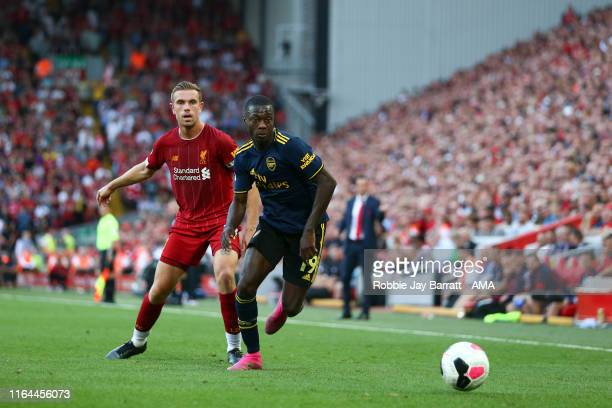 Jordan Henderson of Liverpool and Nicolas Pepe of Arsenal during the Premier League match between Liverpool FC and Arsenal FC at Anfield on August 24...