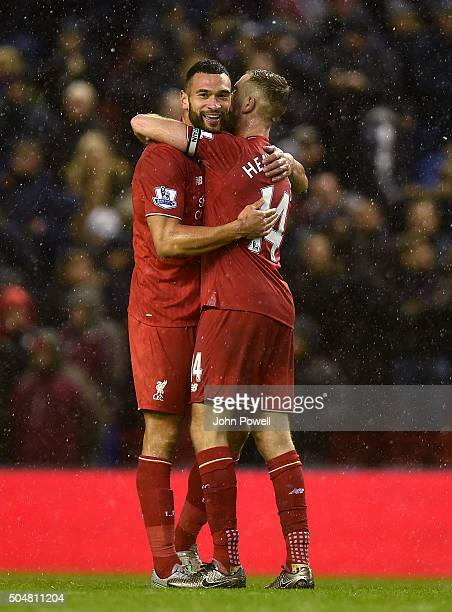 Jordan Henderson of Liverpool and Steven Caulker of Liverpool hug at the end of the Barclays Premier League match between Liverpool and Arsenal at...