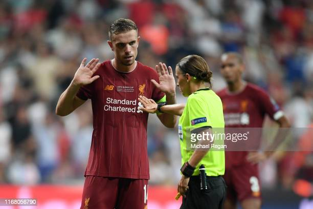 Jordan Henderson of Liverpool argues with referee Stephanie Frappart after a penalty was awarded to Chelsea during the UEFA Super Cup match between...