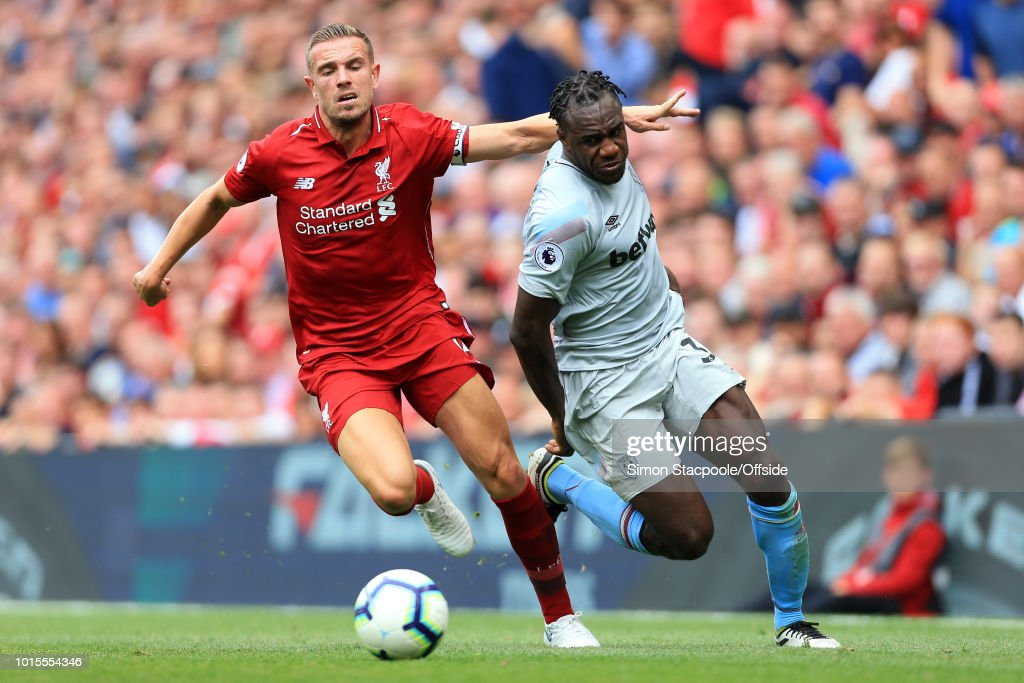 Jordan Henderson of Liverpool battles with Michail Antonio of West Ham during the Premier League match between Liverpool and West Ham United at Anfield on August 12, 2018 in Liverpool, England.