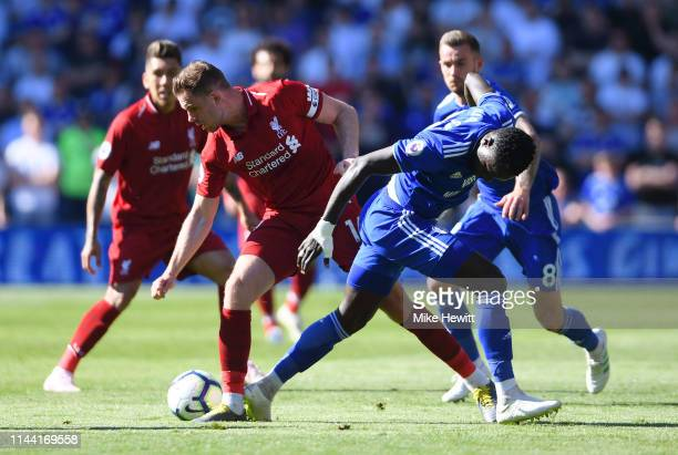 Jordan Henderson of Liverpool battles with Oumar Niasse of Cardiff City during the Premier League match between Cardiff City and Liverpool FC at...