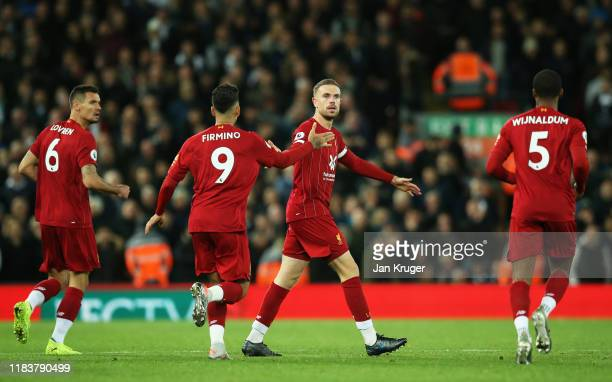 Jordan Henderson of Liverpool celebrates after scoring his team's first goal with Roberto Firmino and team mates during the Premier League match...