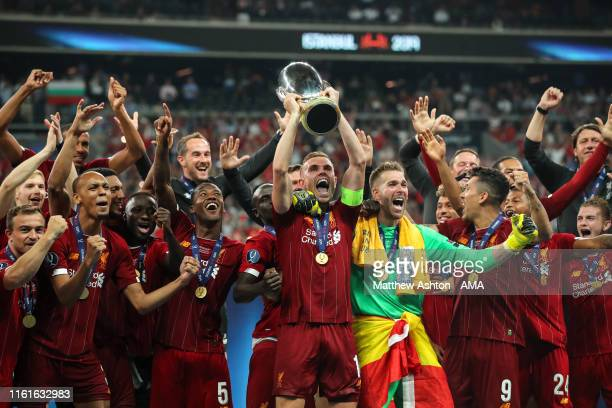 Jordan Henderson of Liverpool celebrates by lifting the UEFA Super Cup trophy during the UEFA Super Cup Final fixture between Liverpool and Chelsea...