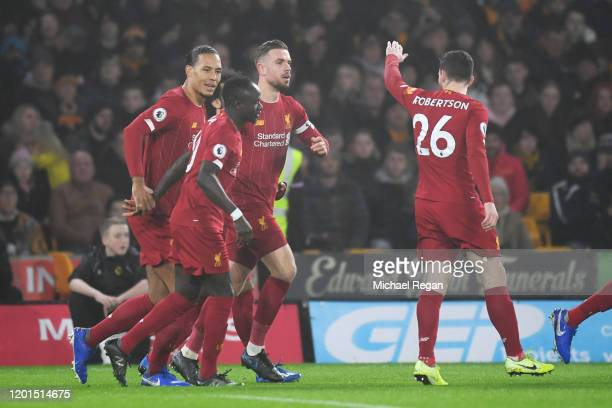 Jordan Henderson of Liverpool celebrates with team-mates after scoring the opening goal during the Premier League match between Wolverhampton...