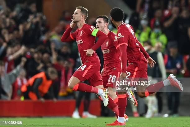 Jordan Henderson of Liverpool celebrates with teammates Joe Gomez and Andrew Robertson after scoring their side's third goal during the UEFA...