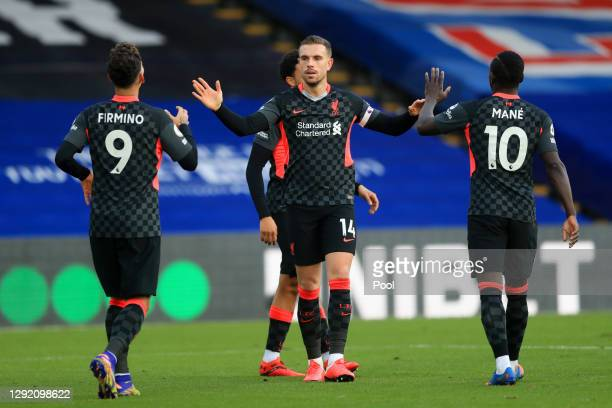 Jordan Henderson of Liverpool celebrates with teammates Sadio Mane and Roberto Firminho after scoring their sides fourth goal during the Premier...