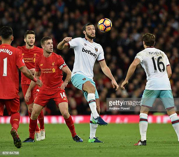Jordan Henderson of Liverpool competes with Andy Carroll of West Ham United during the Premier League match between Liverpool and West Ham United at...