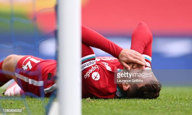 Jordan Henderson of Liverpool holds his face after a collision during the Premier League match between Everton and Liverpool at Goodison Park on...