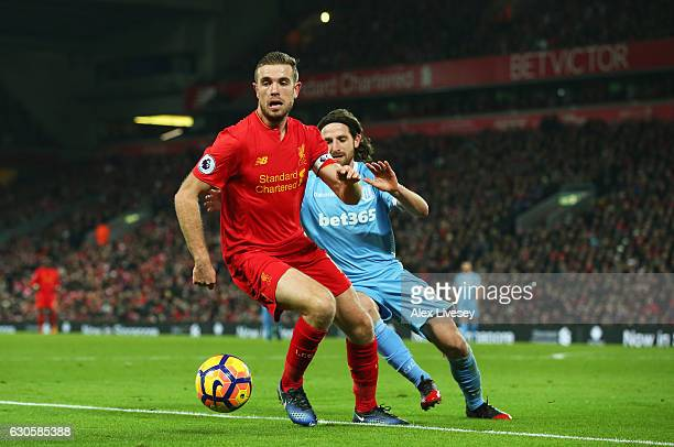Jordan Henderson of Liverpool holds off Joe Allen of Stoke City during the Premier League match between Liverpool and Stoke City at Anfield on...