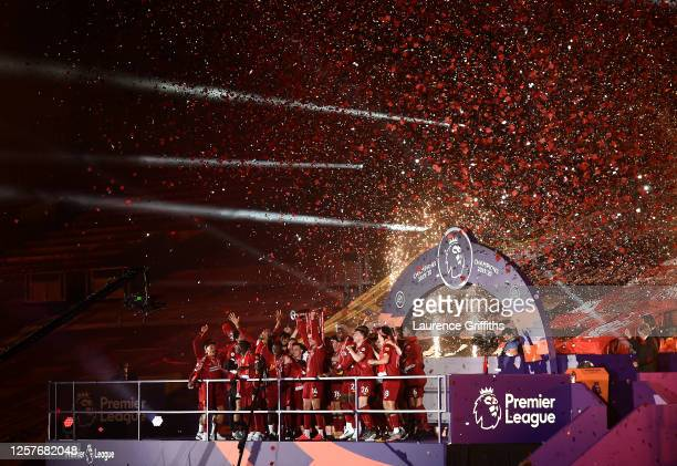 Jordan Henderson of Liverpool holds the Premier League Trophy aloft as they celebrate winning the League during the Premier League match between...