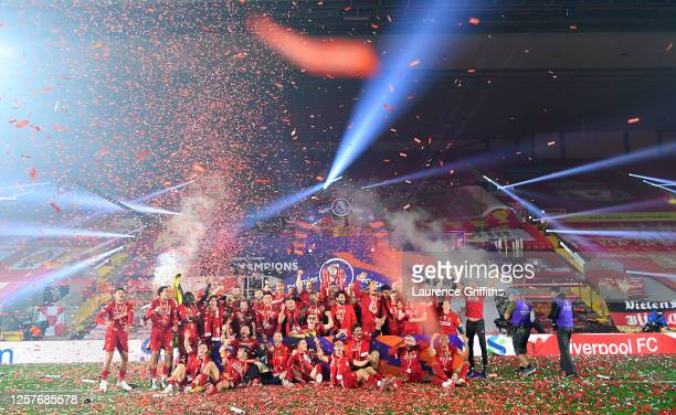 Jordan Henderson of Liverpool holds the Premier League Trophy aloft as the team celebrate winning the League during the presentation ceremony of the...