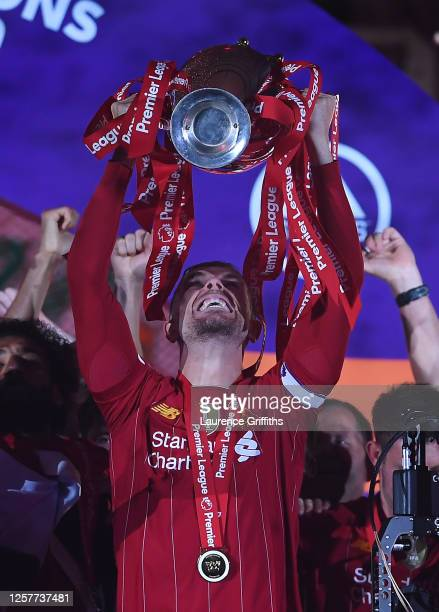 Jordan Henderson of Liverpool holds the Premier League Trophy aloft as the team celebrate winning the Premier League during the presentation ceremony...