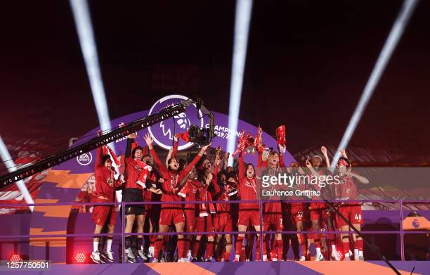 Jordan Henderson of Liverpool holds the Premier League Trophy aloft as they celebrate winning the League during the presentation ceremony of the...