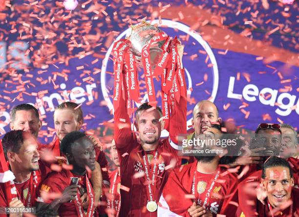 Jordan Henderson of Liverpool holds the Premier League Trophy aloft along side Mohamed Salah as they celebrate winning the League during the...