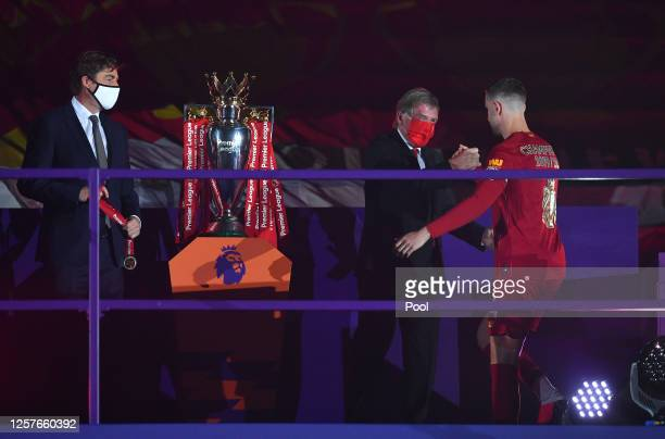 Jordan Henderson of Liverpool interacts with Sir Kenny Dalglish Former Captain and Manager of Liverpool upon receiving The Premier League Trophy...