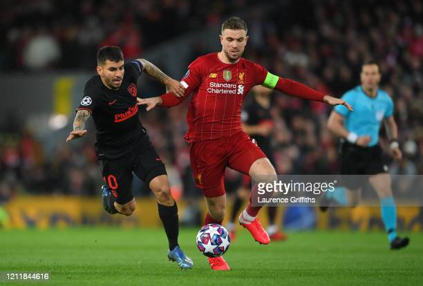 Jordan Henderson of Liverpool is challenged by Angel Correa of Atletico Madrid during the UEFA Champions League round of 16 second leg match between...