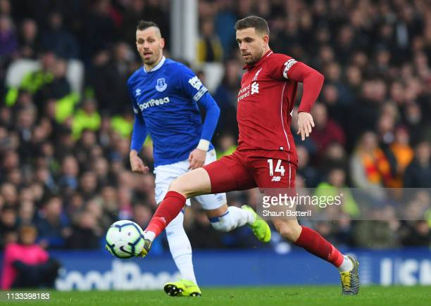 Jordan Henderson of Liverpool is watched by Morgan Schneiderlin of Everton during the Premier League match between Everton FC and Liverpool FC at...