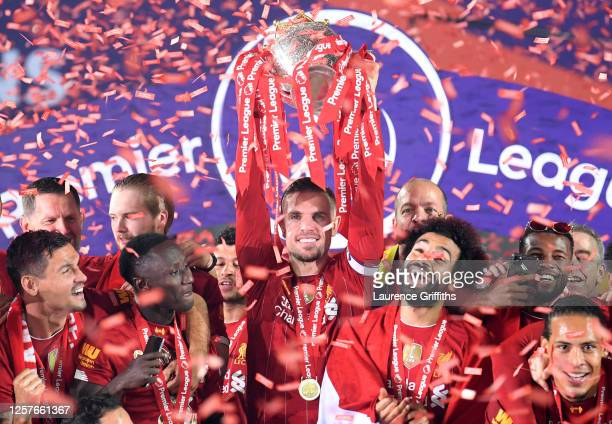 Jordan Henderson of Liverpool lifts The Premier League trophy following the Premier League match between Liverpool FC and Chelsea FC at Anfield on...