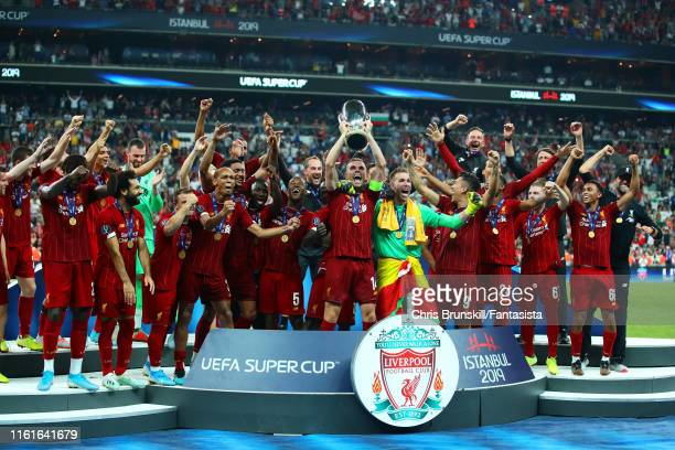 Jordan Henderson of Liverpool lifts the trophy with his team-mates at the end of the UEFA Super Cup match between Liverpool and Chelsea at Vodafone...