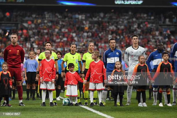 Jordan Henderson of Liverpool lines up next to the match officials Stephanie Frappart Manuela Nicolosi and Michelle O'Neill prior to the UEFA Super...