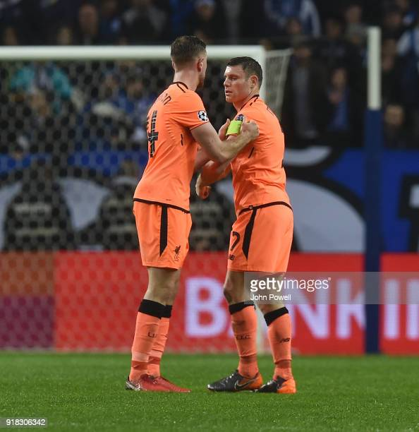 Jordan Henderson of Liverpool passes the captain's armband over to James Milner during the UEFA Champions League Round of 16 First Leg match between...