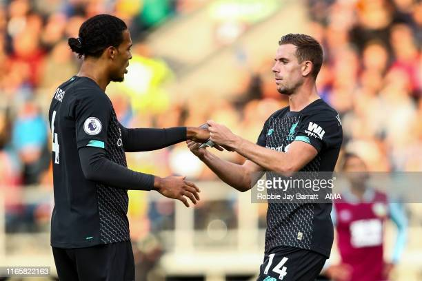 Jordan Henderson of Liverpool passes Virgil Van Dijk of Liverpool the captains arm band during the Premier League match between Burnley FC and...