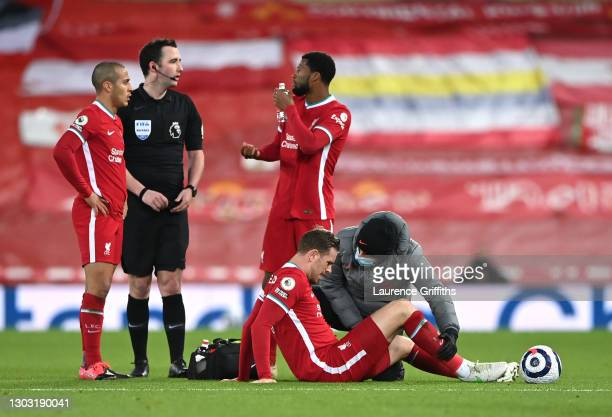 Jordan Henderson of Liverpool receives medical treatment during the Premier League match between Liverpool and Everton at Anfield on February 20,...