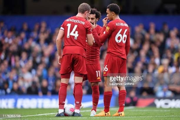 Jordan Henderson of Liverpool stands over a free kick with teammates Mohamed Salah and Trent Alexander-Arnold prior to Trent Alexander-Arnold's goal...
