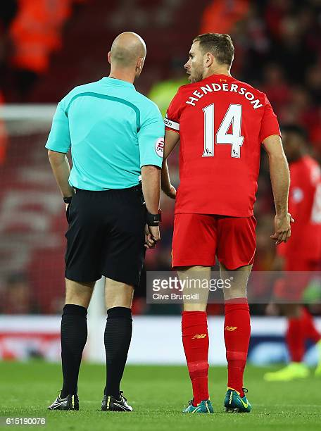 Jordan Henderson of Liverpool talks with referee Anthony Taylor during the Premier League match between Liverpool and Manchester United at Anfield on...