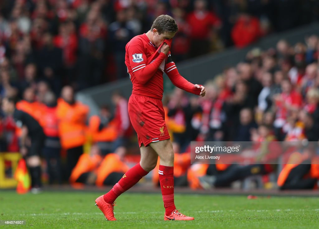 Jordan Henderson of Liverpool walks off after being shown a red card by Referee Mark Clattenburg during the Barclays Premier League match between Liverpool and Manchester City at Anfield on April 13, 2014 in Liverpool, England.