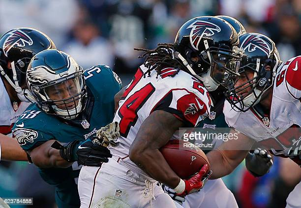 Jordan Hicks of the Philadelphia Eagles attempts to grab Devonta Freeman of the Atlanta Falcons during a game at Lincoln Financial Field on November...