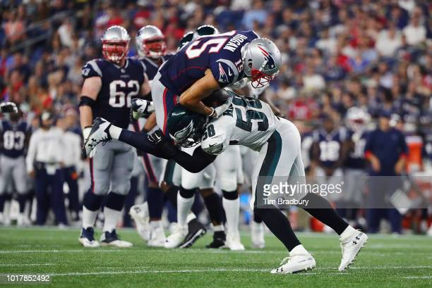 Jordan Hicks of the Philadelphia Eagles tackles Chris Hogan of the New England Patriots in the first half during the preseason game at Gillette...