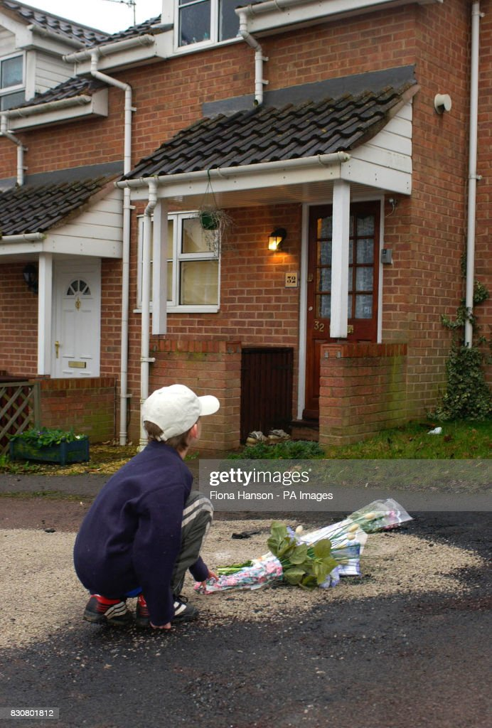 Jordan Hill, aged eight, leaves flowers outside the house in Colmworth close, Reading, where 2 children were killed in a car fire. The children, a girl aged three and her one-year-old brother, were rushed to the Royal Berkshire Hospital in Reading. *..., after being pulled free from the blazing car by their parents but died from their severe injuries in hospital. It is understood that the children's parents left them in the parked vehicle for a few minutes while they visited friends.