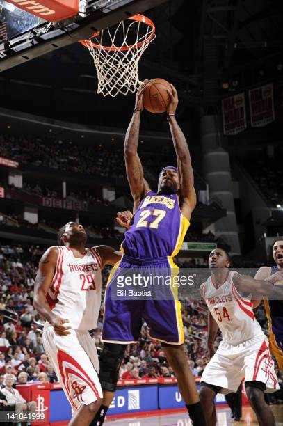 Jordan Hill of the Los Angeles Lakers goes to the basket against Marcus Camby and Patrick Patterson of the Houston Rockets during the game between...