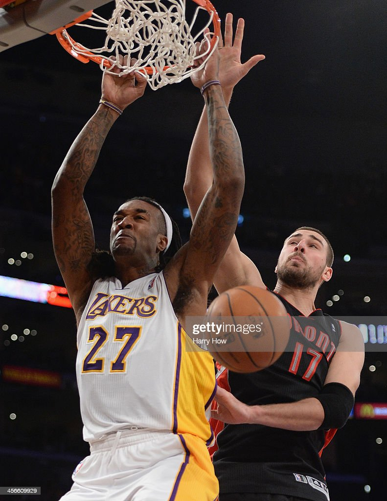 Jordan Hill #27 of the Los Angeles Lakers scores on a dunk past Jonas Valanciunas #17 of the Toronto Raptors at Staples Center on December 8, 2013 in Los Angeles, California.